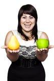 Mujer joven que sostiene una manzana y una pera imagen de archivo