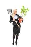 Mujer joven que sostiene una pala y una planta Imagenes de archivo