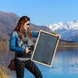 Mujer joven que sostiene una pizarra Fotografía de archivo libre de regalías