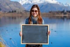 Mujer joven que sostiene una pizarra Fotografía de archivo