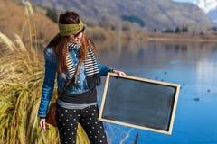Mujer joven que sostiene una pizarra Imagenes de archivo