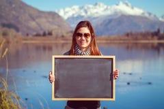 Mujer joven que sostiene una pizarra Fotos de archivo