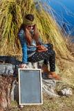 Mujer joven que sostiene una pizarra Foto de archivo libre de regalías