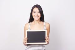 Mujer joven que sostiene una pizarra Imagen de archivo libre de regalías