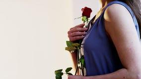 Mujer joven que sostiene una rosa roja Imagenes de archivo