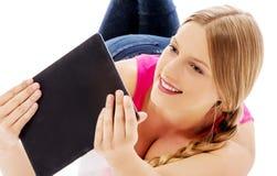 Mujer joven que sostiene una tableta digital Fotos de archivo