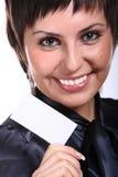 Mujer joven que sostiene una tarjeta blanca. Foto de archivo libre de regalías