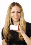 Mujer joven que sostiene una tarjeta en blanco Fotografía de archivo libre de regalías
