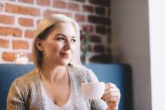 Mujer joven que sostiene una taza de café Fotos de archivo libres de regalías