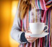 Mujer joven que sostiene una taza de café en café Fotografía de archivo libre de regalías