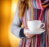 Mujer joven que sostiene una taza de café en café Imagen de archivo libre de regalías