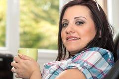Mujer joven que sostiene una taza de café en casa Foto de archivo