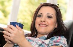 Mujer joven que sostiene una taza de café en casa Imagen de archivo