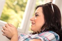 Mujer joven que sostiene una taza de café en casa Imagen de archivo libre de regalías