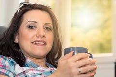 Mujer joven que sostiene una taza de café en casa, efecto luminoso Imagenes de archivo
