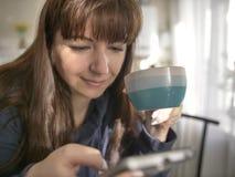 Mujer joven que sostiene una taza de café y que usa el teléfono en la cocina foto de archivo