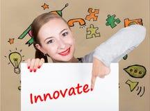 Mujer joven que sostiene whiteboard con palabra de la escritura: innove Tecnología, Internet, negocio y márketing Imagen de archivo