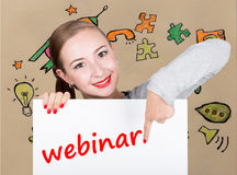 Mujer joven que sostiene whiteboard con palabra de la escritura: webinar Tecnología, Internet, negocio y márketing Imagen de archivo libre de regalías