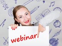 Mujer joven que sostiene whiteboard con palabra de la escritura: webinar Tecnología, Internet, negocio y márketing Fotografía de archivo libre de regalías