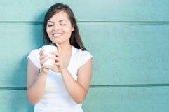 Mujer joven que sostiene y que mira el café para llevar Imagen de archivo libre de regalías