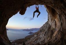 Mujer joven que sube en cueva en la puesta del sol Fotografía de archivo libre de regalías