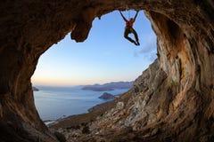 Mujer joven que sube en techo en cueva en la puesta del sol Fotografía de archivo
