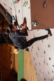 Mujer joven que sube para arriba en la pared de la práctica en gimnasio Imagenes de archivo