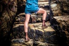 Mujer joven que sube una roca Fotografía de archivo libre de regalías