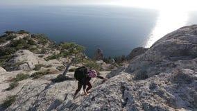 Mujer joven que sube y que alcanza el top de una montaña Señora en la cumbre en el paisaje hermoso que hace frente a la costa almacen de metraje de vídeo