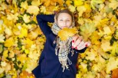 Mujer joven que sueña en hojas de otoño Imágenes de archivo libres de regalías
