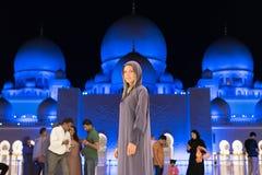 Mujer joven que sueña en la mezquita magnífica de Sheikh Zayed Mosque en el abaya que lleva de Abu Dhabi, paranja en noche travel Foto de archivo