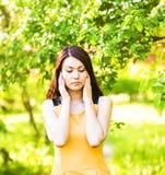 Mujer joven que sufre con dolor de cabeza al aire libre Imagen de archivo