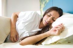 Mujer joven que sufre de dolor abdominal imagenes de archivo