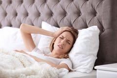 Mujer joven que sufre de dolor de cabeza mientras que miente Imagenes de archivo