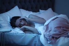Mujer joven que sufre de dolor de cabeza mientras que miente en cama Fotografía de archivo libre de regalías