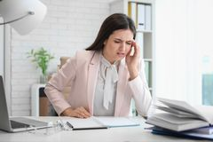 Mujer joven que sufre de dolor de cabeza mientras que se sienta en la tabla Fotos de archivo libres de regalías