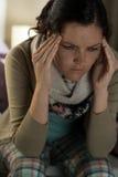 Mujer joven que sufre de dolor de cabeza Foto de archivo