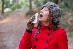 Mujer joven que sufre de un frío, de una gripe o de alergias Foto de archivo libre de regalías
