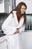 Mujer joven que sufre del dolor del abdomen que se coloca en cocina Foto de archivo libre de regalías