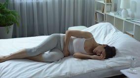 Mujer joven que sufre del dolor severo y del calambre en un abdomen más bajo, menstruación metrajes