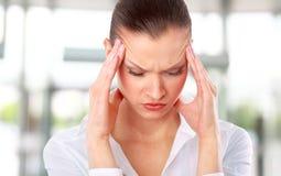 Mujer joven que sufre un dolor de cabeza Foto de archivo