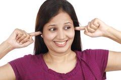 Mujer joven que tapa los oídos con los fingeres Imagen de archivo libre de regalías