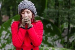 Mujer joven que tiembla con frío en un bosque Imagenes de archivo