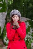 Mujer joven que tiembla con frío en un bosque Foto de archivo