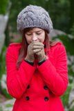 Mujer joven que tiembla con frío en un bosque Fotos de archivo