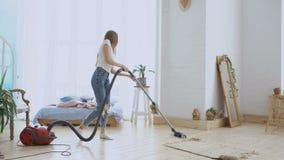 Mujer joven que tiene casa de la limpieza de la diversión con el aspirador que baila y que canta en casa metrajes