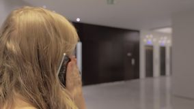Mujer joven que tiene charla del teléfono que camina en pasillo del hotel almacen de video