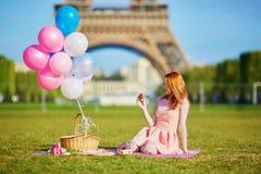 Mujer joven que tiene comida campestre cerca de la torre Eiffel en París, Francia Imágenes de archivo libres de regalías