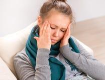 Mujer joven que tiene dolor de cabeza Imágenes de archivo libres de regalías