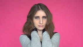 Mujer joven que tiene dolor en cuello sobre fondo rosado almacen de metraje de vídeo